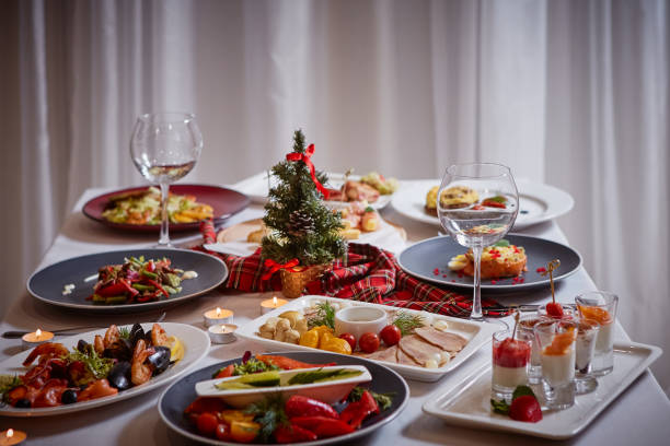 Christmas themed dinner table with a variety of appetizers and salads stock photo
