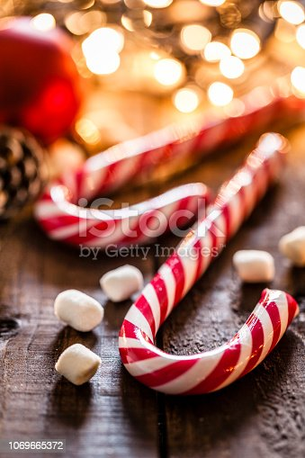 Close up view of two candy canes shot on rustic wooden table. Some marshmallows are on the table and Christmas lights are out of focus at background. Predominant colors are red and yellow. Low key DSRL studio photo taken with Canon EOS 5D Mk II and Canon EF 100mm f/2.8L Macro IS USM.