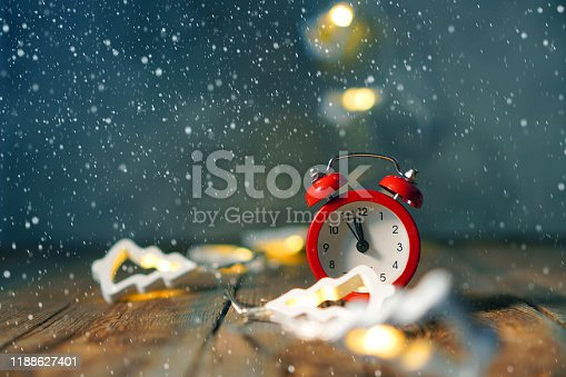 816405814 istock photo Christmas time background with red clock and garland on a wooden table 1188627401