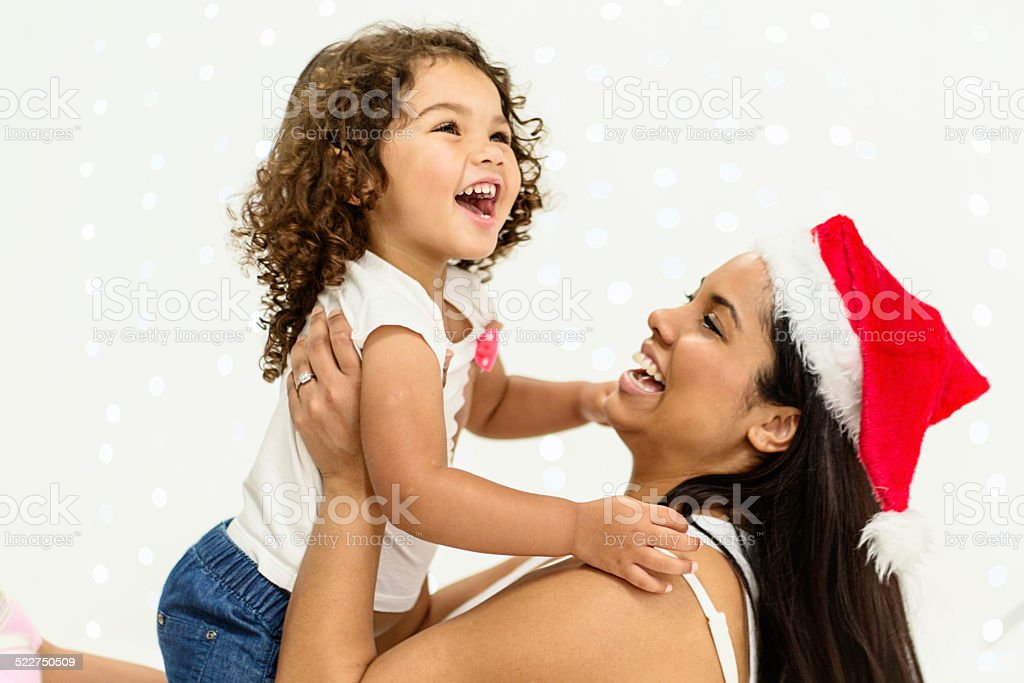 Christmas time! Excited little girl with Mum in Santa hat stock photo