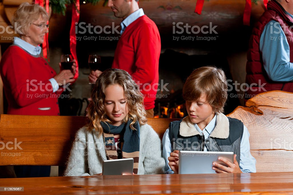 Christmas Time Girl and boy sitting at the table and using digital tablets with adults standing by fireplace in the background. Active Seniors Stock Photo