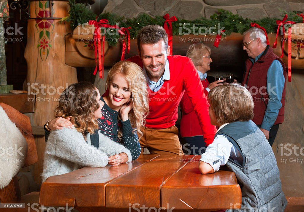 Christmas Time Happy parents talking with their children at the table at home with granparents standing by the fireplace in the background.  Active Seniors Stock Photo