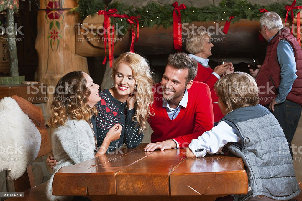Christmas Time Happy parents talking with their children at the table at home with granparents standing by the fireplace in the background and drinking wine. Active Seniors Stock Photo
