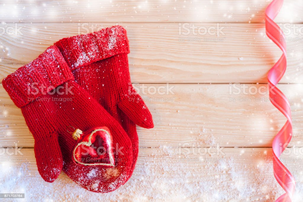 Christmas toy heart is laying on red knitted mittens on wooden table with snow, copy space and red wavy ribbon. stock photo