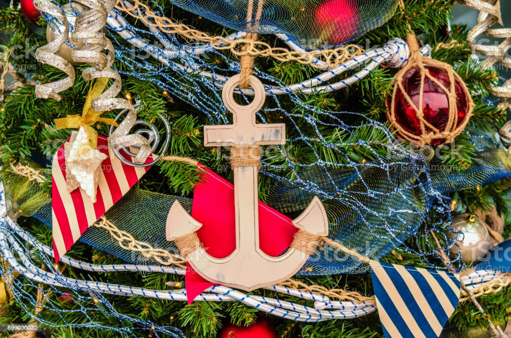 Christmas toys, an anchor, a star, balls and flags on a Christmas tree stock photo