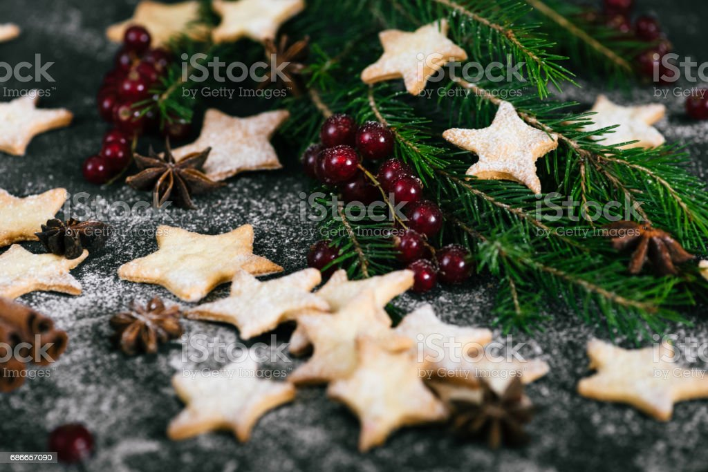 Christmas traditional star shaped cookies with red currant berries and spruce on the table royalty-free stock photo