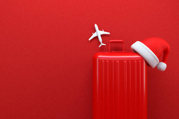 Christmas Travel Concept with Suitcase on Red Background stock photo