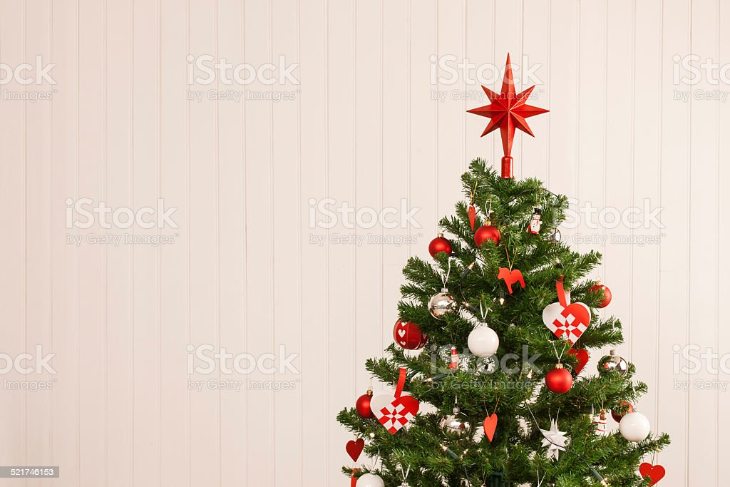 Christmas tree against a wooden wall stock photo
