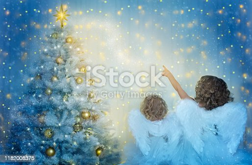 istock Christmas Tree and Children Looking to Star, Kids with Wings as Xmas Angels in Night Lights 1182008375