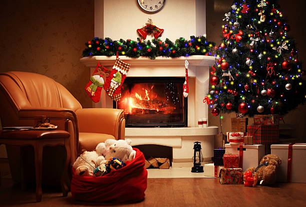 christmas tree and christmas gift boxes in interior with fireplace - weihnachtsstadt stock-fotos und bilder
