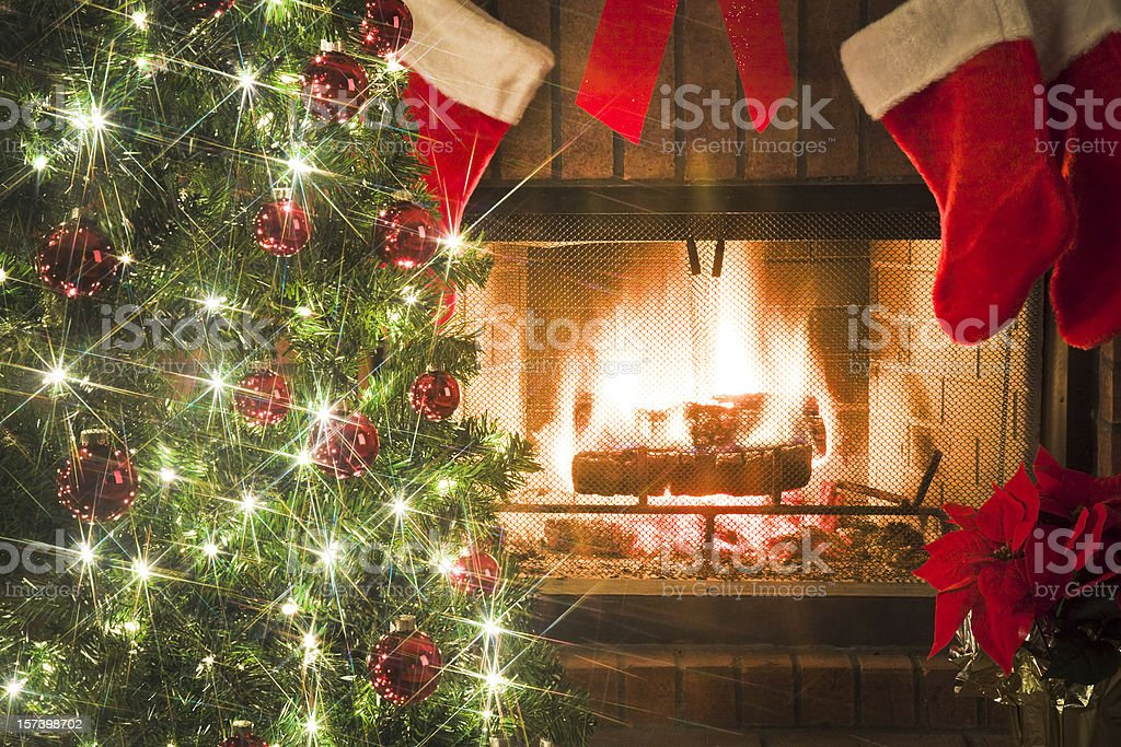 Christmas tree and decor around the fireplace with blazing fire royalty-free stock photo