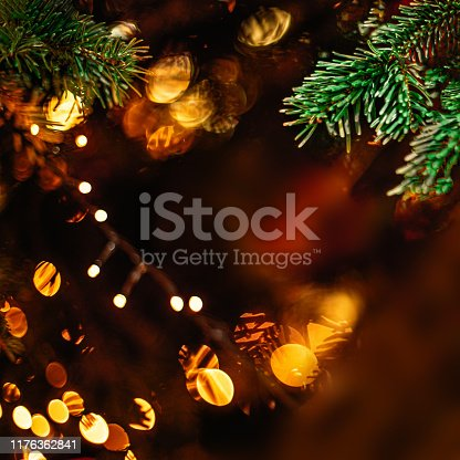istock Christmas tree and  decorations with abstract sparkling lights. Red ball, golden bokeh lights, ribbon in dark tones 1176362841
