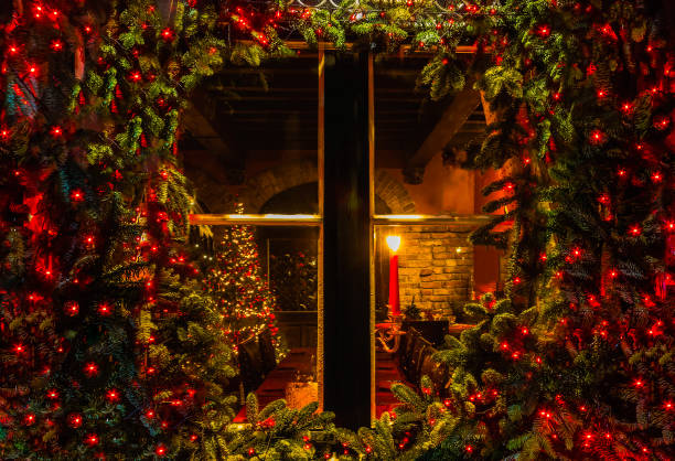 Christmas tree and fireplace seen through a wooden cabin window Christmas tree and fireplace seen through a wooden cabin window outdoor passenger cabin stock pictures, royalty-free photos & images