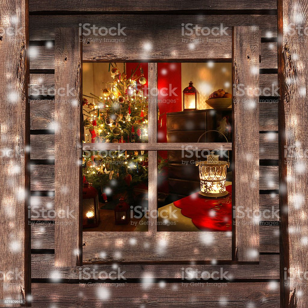 Christmas tree and fireplace seen through a wooden cabin window stock photo