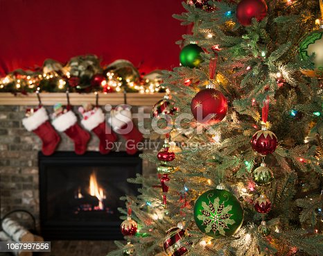 Christmas tree against a fireplace with stockings and copy space
