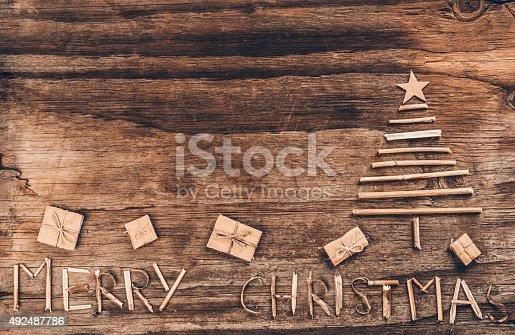 527392693 istock photo Christmas tree and gift box on vintage wood 492487786