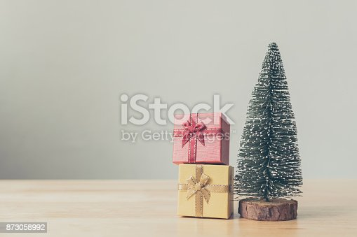 istock Christmas tree and gift box red, yellow color on wood table with white wall background, Christmas holiday celebration and boxing day concept, Copy space 873058992