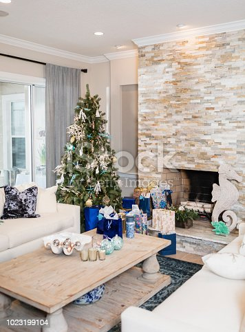 A living room with Christmas tree and gifts. The ornaments are beach-themed seashells, starfish and coral.