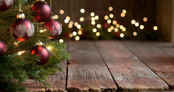 Christmas tree with baubles and lights against an old wood background