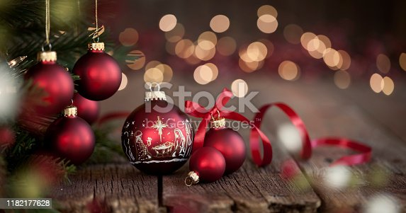 Christmas tree with red baubles & nativity Christmas ornaments on an old wood background with defocused lights