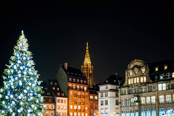Christmas Tree and Notre-Dame cathedral at night Christmas market atmosphere with majestic Christmas Tree and the illuminated Notre-Dame Cathedral - seen from Place Kleber in Strasbourg, France Alsace strasbourg stock pictures, royalty-free photos & images