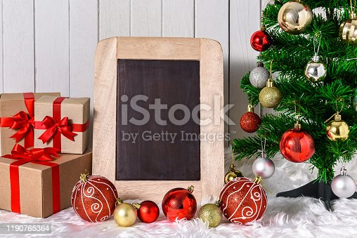Close up Christmas tree and ornaments with gifts boxes and chalkboard on white fur and white wooden background