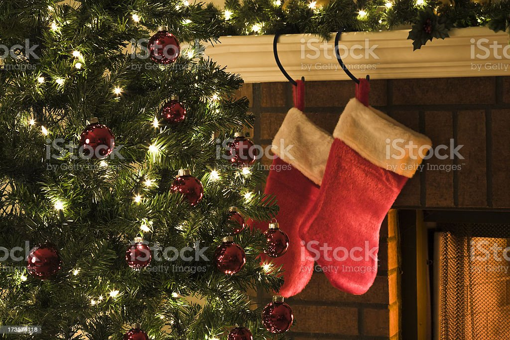Christmas tree, and stockings hanging from mantel by fireplace stock photo