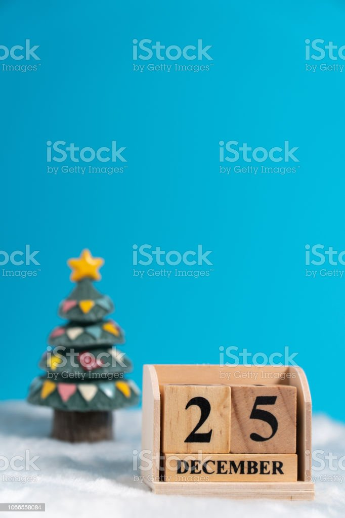 Christmas tree backside wooden block calendar set on the Christmas date 25 december on white wool and blue background. Copy space for text or content. Concept of 25/12 merry christmas. stock photo