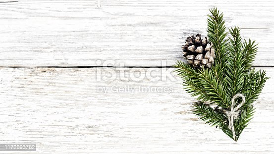 Fir branch and pine cone on white wooden plank christmas background.