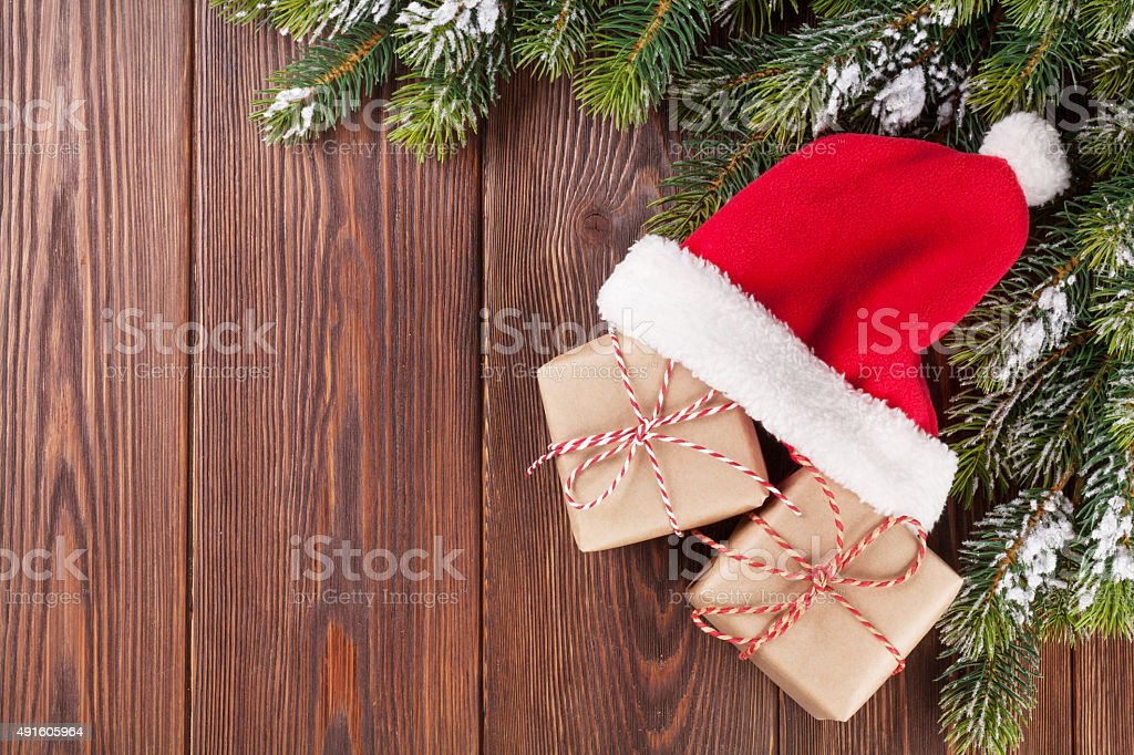Christmas tree branch and santa hat with gifts stock photo