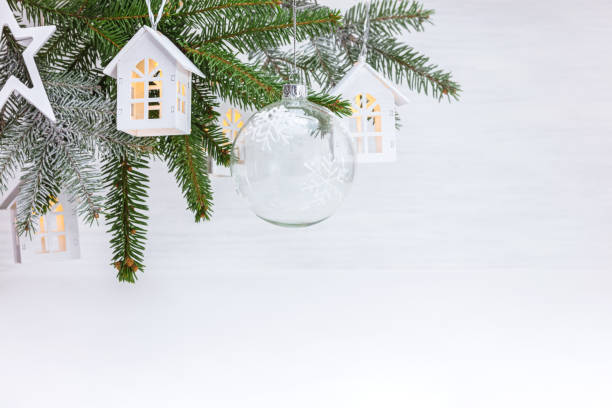 christmas tree branch decorated with glass ball, wooden decorative toys house garland and star stock photo