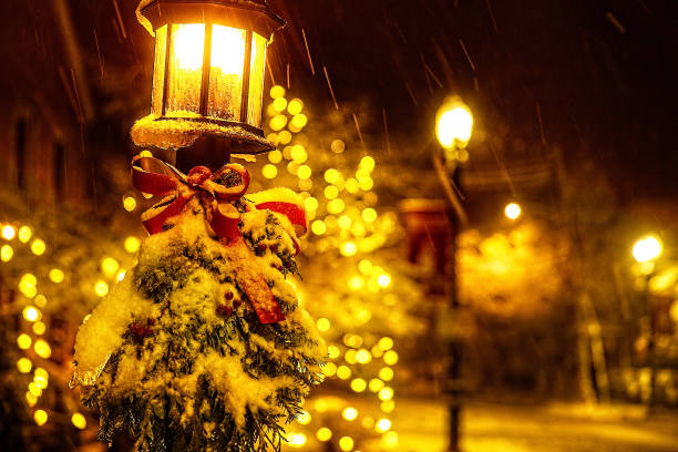 Christmas tree branches and a red bow on a lantern under a falling snow stock photo