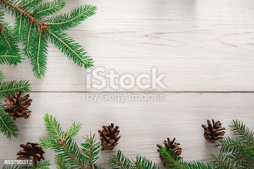 Christmas decoration, frame concept background, top view with copy space on white rustic wood table surface. Christmas ornaments border with fir tree branches and cones