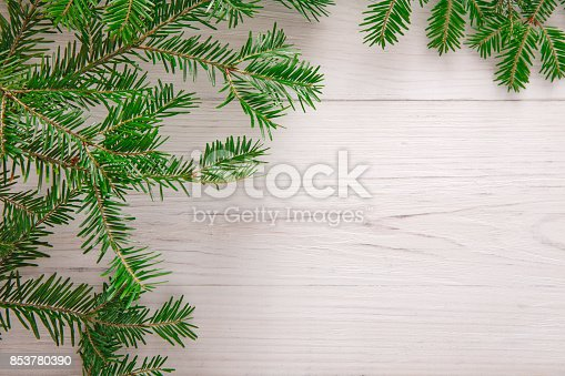 Christmas decoration, frame concept background, top view with copy space on white wood table surface. Christmas ornaments border with fir tree branches