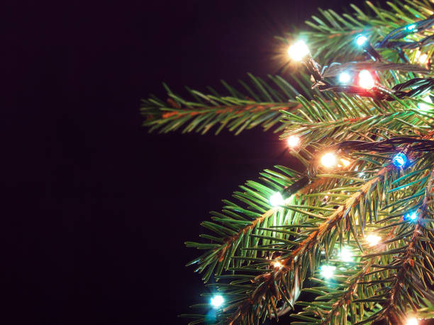 christmas tree decked with glowing garland on a dark background - light through trees stock pictures, royalty-free photos & images