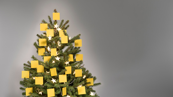 Christmas tree decorated with 25 blank yellow post-it notes