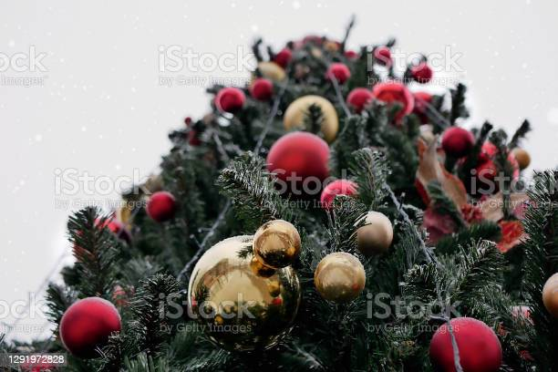 Photo of Christmas tree decorated with red and yellow balls lightly covered with snow outdoors