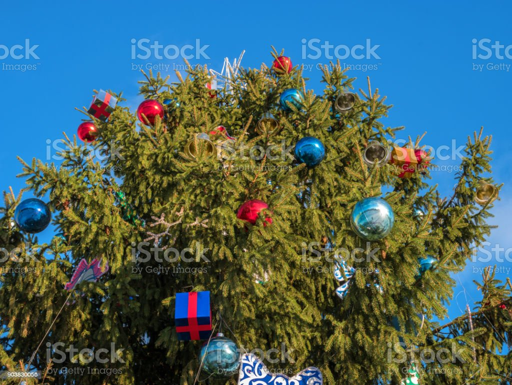 Christmas tree decorated with toys. Tree stands on the street. Top Christmas tree with toys large. stock photo