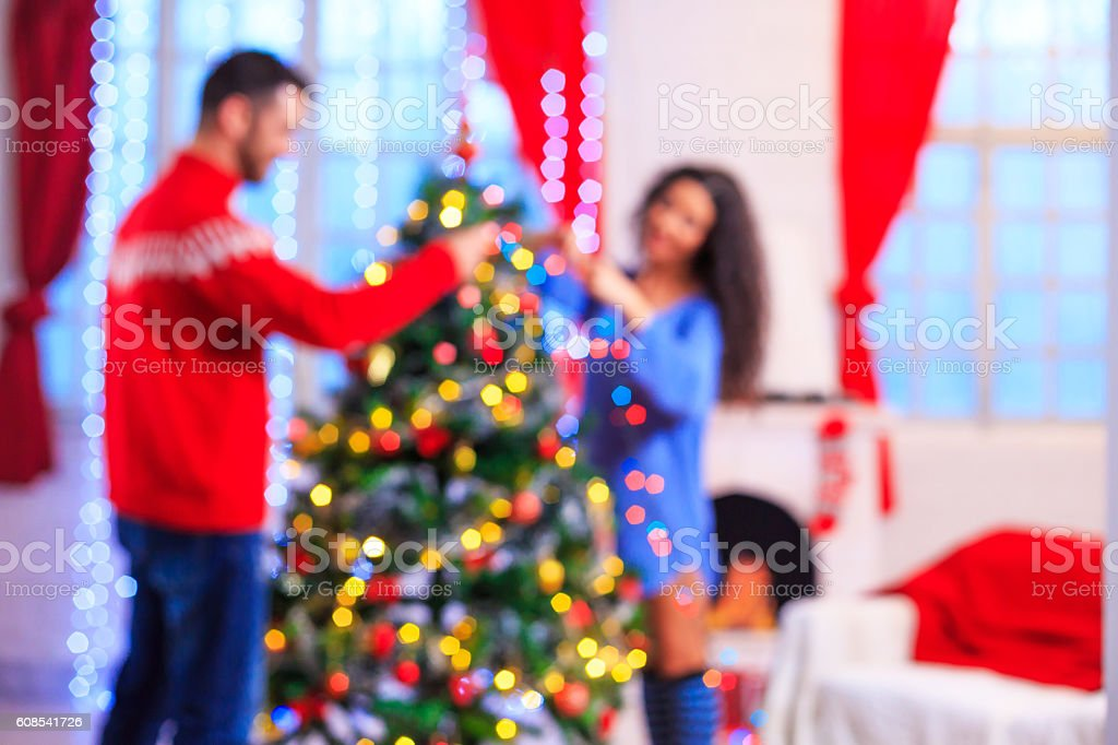 Cheerful young couple decorating the christmas tree at home. Man...