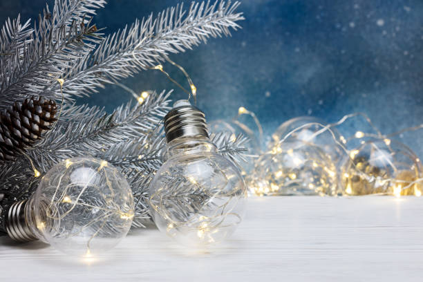 christmas tree decorations and old lamp garland for illumination on blurred blue background stock photo