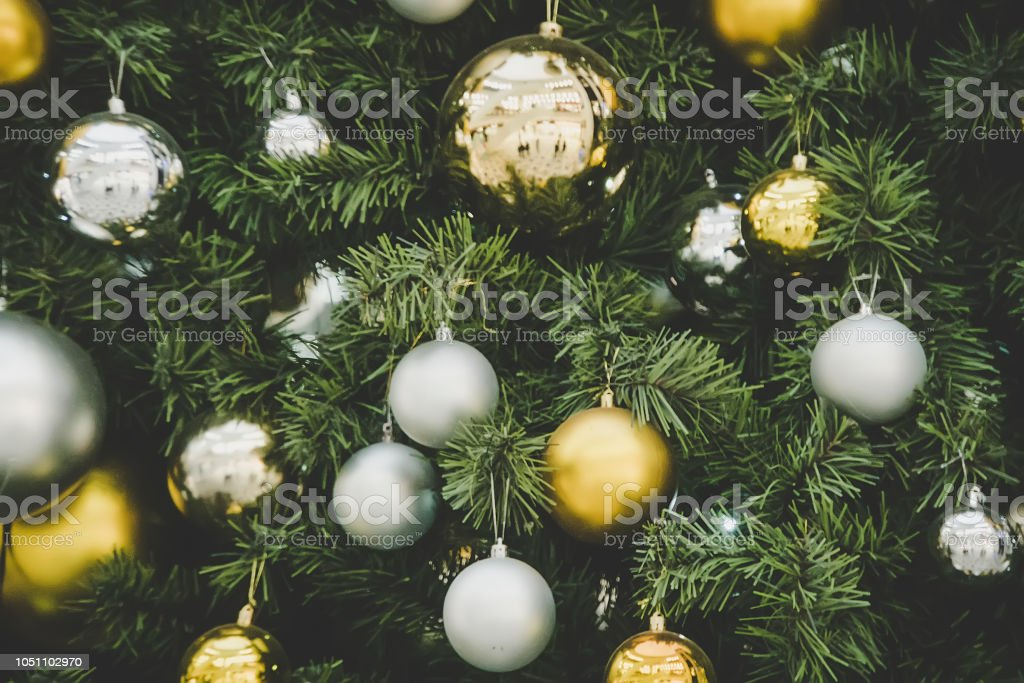 christmas-tree-decorations-gold-and-silver-balls-hanging-on-the-green-picture-id1051102970