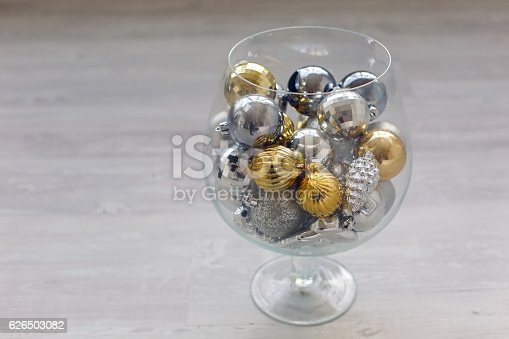 Christmas tree decorations in a glass vase standing on the floor