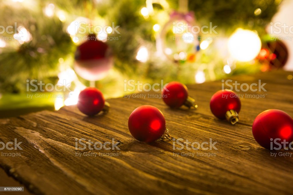 Christmas tree decorations red balls laying on a rustic wooden table ready to be hanged on a Christmas tree stock photo