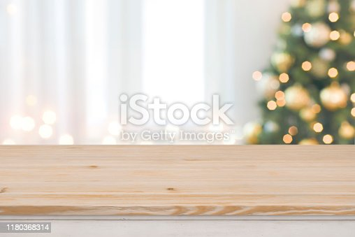 Christmas tree defocused background with wooden table in front