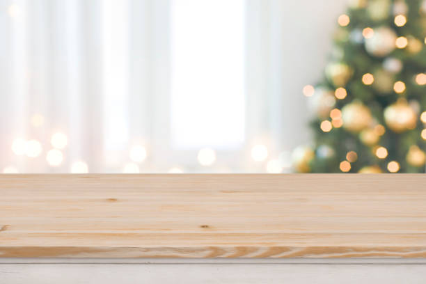 Christmas tree defocused background with wooden table in front stock photo