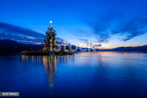 Christmas tree on a pontoon, floating on lake Woerthersee in Austria. Long exposure - smooth water.