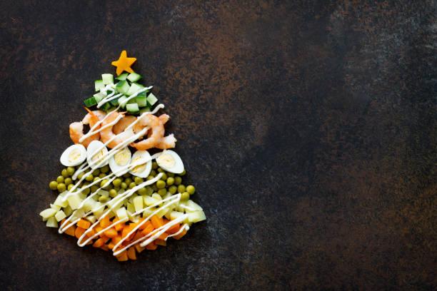 weihnachtsbaum aus einem salat olivier auf einem braunen rostigen stein oder metall hintergrund. ansicht von oben mit einer kopie. - weihnachtsessen ideen stock-fotos und bilder