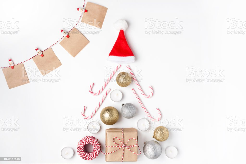 Christmas tree from golden and silver balls, gift, candles, lollipops, red hat santa claus, notes with wish on clothespins, Top view White Background Christmas New Year stock photo