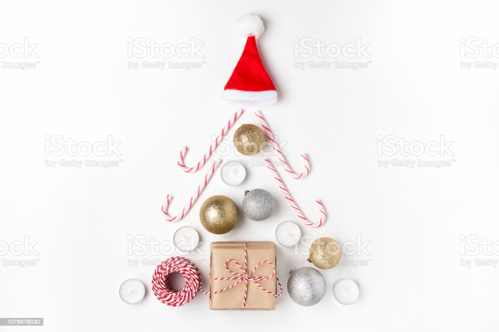 Christmas tree from golden and silver balls, gift, candles, lollipops, red hat santa claus Top view White Background Christmas New Year stock photo