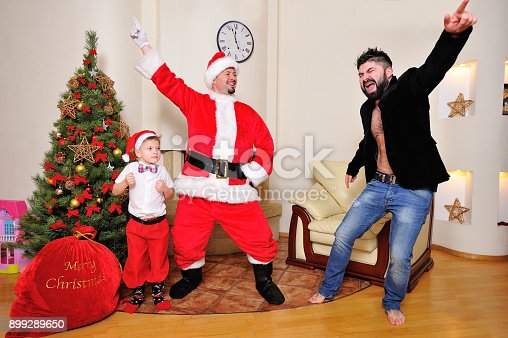 istock Christmas tree, gift bag, fireplace - men dressed as Santa, boy in red pants and high socks and a hipster in velours jacket on bare torso dancing, play the fool. 899289650